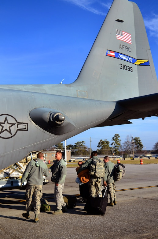 Deploying members of the 94th Airlift Wing bring their personal bags to the back of the C-130H for loading prior to takeoff for their Southwest Asia deployment, Jan. 5, 2015 at Dobbins Air Reserve Base, Ga.  (U.S. Air Force photo/Brad Fallin)