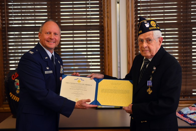 U.S. Air Force Col. Jim Jones, 121st Air Refueling Wing Commander, presents retired Staff Sgt. Jesse Reese with the Distinguished Flying Cross medal Jan. 16, 2015, in Dover, Ohio. Reese earned the medal on Dec. 31, 1944,  as a tail gunner over the skies of Hamburg, Germany. (U.S. Air National Guard photo by Master Sgt. Ralph Branson/Released)