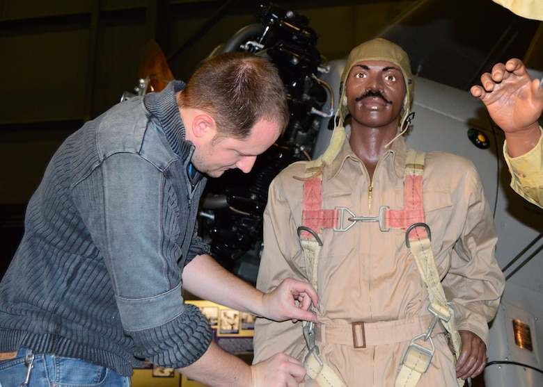 DAYTON, Ohio -- Exhibits Specialist Luke Maynard works on installing the mannequins in the Tuskegee Airmen diorama in the WWII Gallery at the National Museum of the U.S. Air Force. (U.S. Air Force photo)