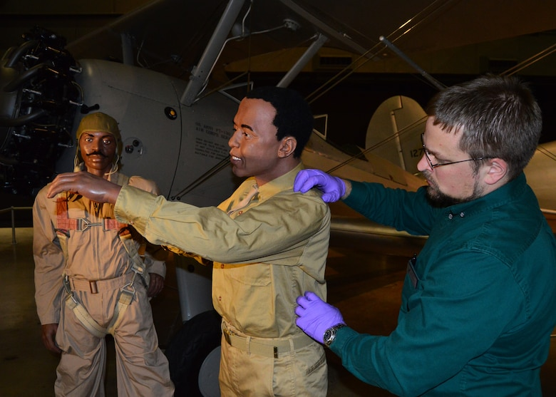 DAYTON, Ohio -- Museum Curator Scott Bradley works on installing the mannequins in the Tuskegee Airmen diorama in the WWII Gallery at the National Museum of the U.S. Air Force. (U.S. Air Force photo)