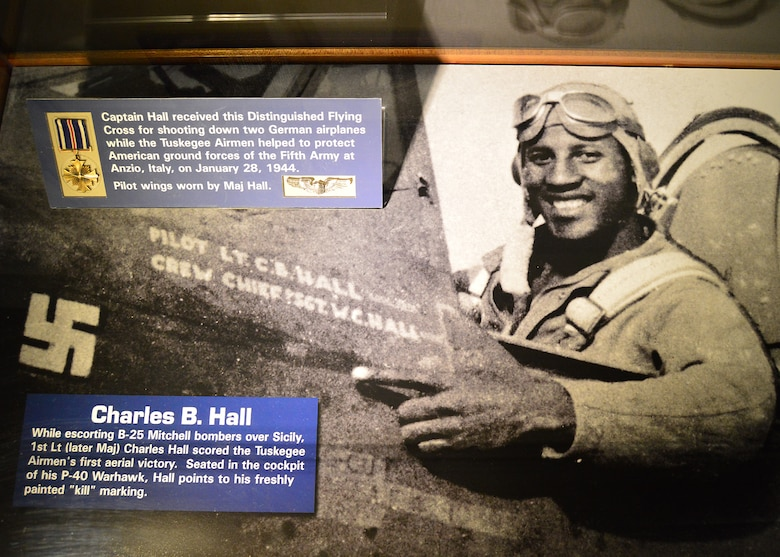 "DAYTON, Ohio -- Charles B. Hall display case in the Tuskegee Airmen Exhibit  in the WWII Gallery at the National Museum of the U.S. Air Force. While escorting B-25 Mitchell bombers over Sicily, 1st Lt (later Maj) Charles Hall scored the Tuskegee Airmen's first aerial victory.  Seated in the cockpit of his P-40 Warhawk, Hall points to his freshly painted ""kill"" marking. (U.S. Air Force photo)"