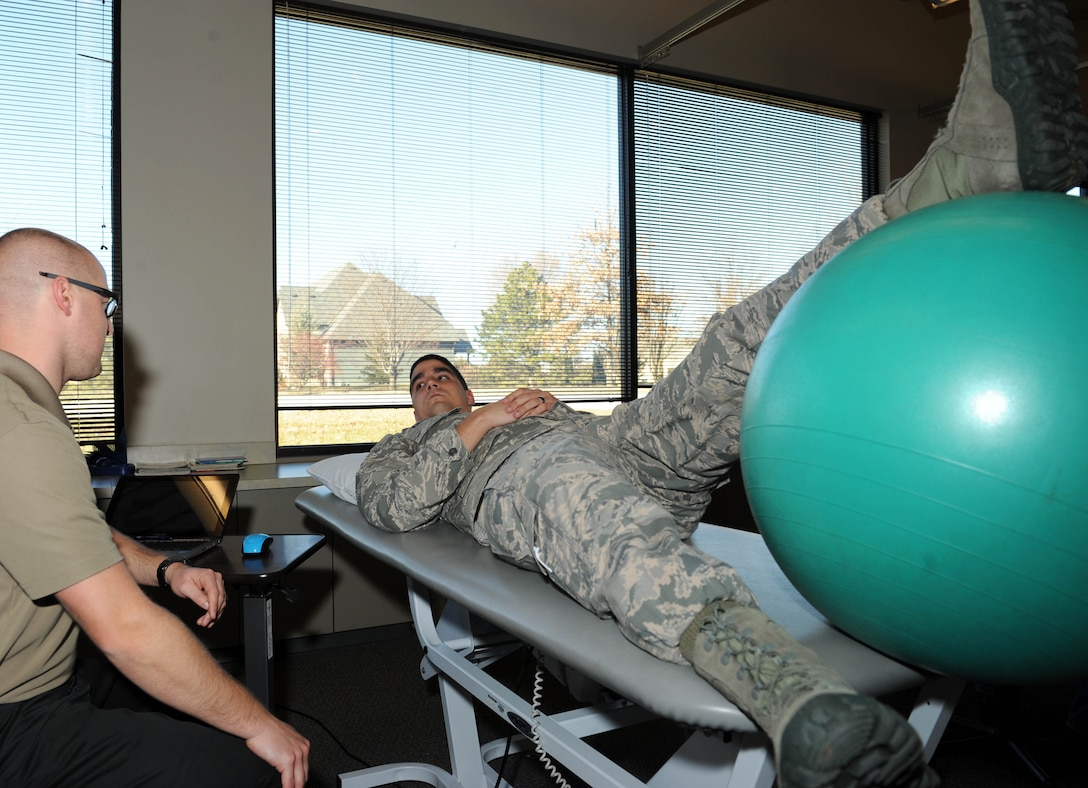 Airman 1st Class Jeffrey Langford, 22nd Security Forces Squadron elite guardsman, listens to Zane Ochs, his physical therapist, during a session, Jan. 15, in Wichita, Kan. Langford tore several ligaments in his knee during an intramural football game and is going through rehab to gain full active status. (U.S. Air Force photo/Airman 1st Class David Bernal Del Agua)
