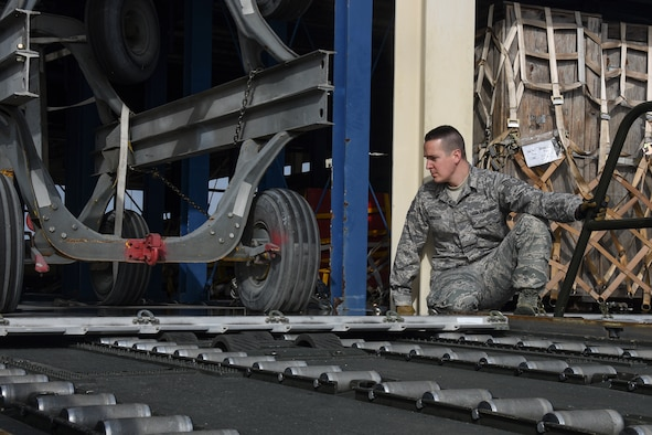 Tech. Sgt. Geoff Monsour, 32nd Aerial Port Squadron ramp operations specialist, watches a piece of cargo as he transfers it onto a loading dock from a 60-thousand pound loader while training at Travis Air Force Base, Calif., Jan. 19. If cargo isn't correctly placed on the loader or the loader isn't correctly lined up with the loading dock equipment may become damaged or get stuck while being transferred. (U.S. Air Force photo by Senior Airman Joshua J. Seybert)