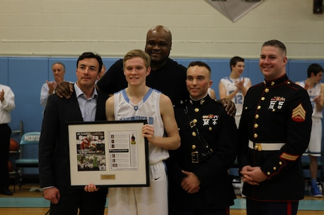 Jack Cadigan, center with plaque, stands with Antoine Walker, Capt. Zachary Johnson, Sgt. Keily Warren, and Stephen Cannella after receiving the Sports Illustrated High School Athlete of the Month award during half time of a varsity basketball game, Jan. 20. Cadigan's father, a cardiologist, found that Jack had a threatening heart abnormality when they were volunteering at a clinic St. Tock, Haiti last August. and Jack underwent surgery upon return to the U.S. Later, Jack heard of a Haitian orphan who had the same heart condition and, after many obstacles, brought her to the States for a life-saving operation. Cadigan is a Medfield High School senior and varsity basketball player. Walker is a former Boston Celtics basketball player. Johnson is the executive officer of Recruiting Station Portsmouth, N.H.; Warren is a canvassing recruiter for Recruiting Substation Framingham. Cannella is an assistant managing editor for Sports Illustrated.