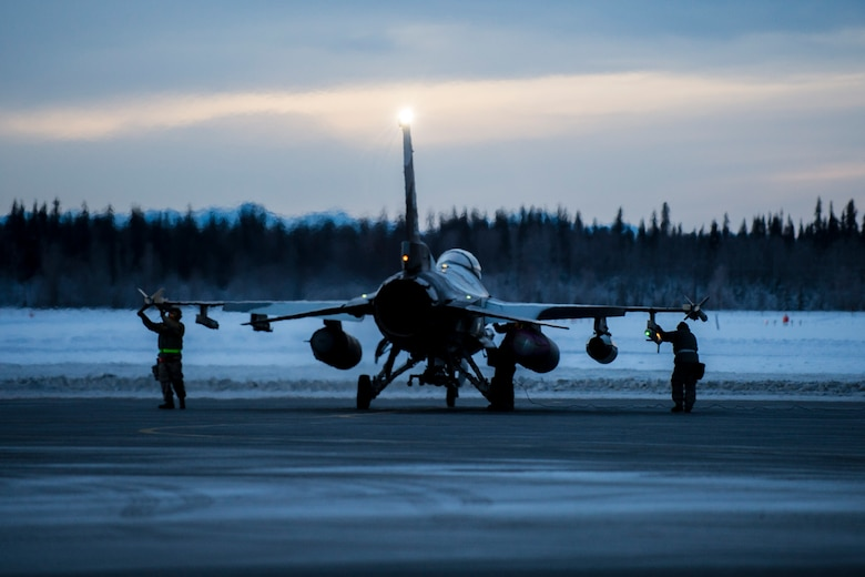 Airmen prepare an F-16 Fighting Falcon aircraft Jan. 17, 2015, on Eielson Air Force Base, Alaska, in transit to Joint Base Pearl Harbor-Hickam, Hawaii, and Andersen Air Force Base, Guam. More than 150 maintainers will keep the 18th Aggressor Squadron in the air during Pacific Air Forces exercises, which are meant to prepare Airmen, Sailors and Marines, along with coalition partners in the Pacific theater, of operations for contingency operations if the need arises. The Airmen are from the 354th Aircraft Maintenance Squadron. (U.S. Air Force photo/Staff Sgt. Joshua Turner)