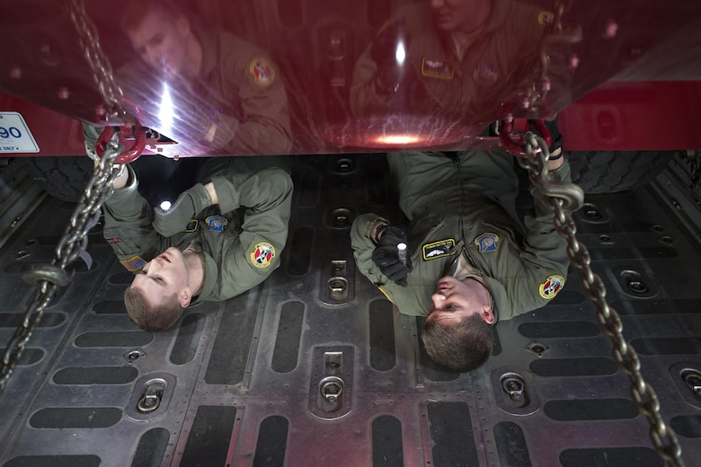 Senior Airmen Christopher Hofer and Dillon Howell inspect chains that secure a P-19 Aircraft Rescue Firefighting Vehicle inside of a C-130 Hercules Jan. 14, 2015, at Yokota Air Base, Japan, during a readiness inspection. The inspection was designed to evaluate areas such a rapid mobility response to simulated contingencies. The Airmen are both 36th Airlift Squadron loadmasters. (U.S. Air Force photo/Osakabe Yasuo)