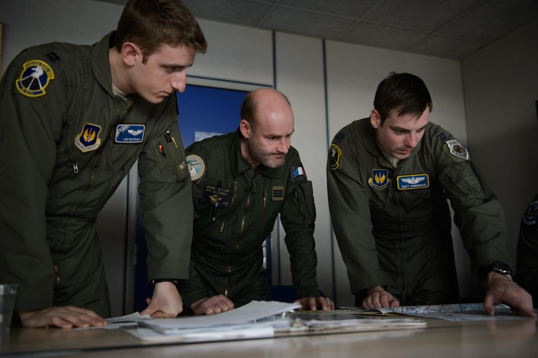Two U.S. Air Force pilots and a French air force navigator discuss the route to the drop zone during a simulated low-level drop Jan. 21, 2015, at Orleans - Bricy Air Base, France. The drop is one of many events during exercise Volfa 15-1, a French-led exercise designed to improve tactical airlift and fighter squadron operation between allied countries. (U.S. Air Force photo/Senior Airman Armando A. Schwier-Morales)
