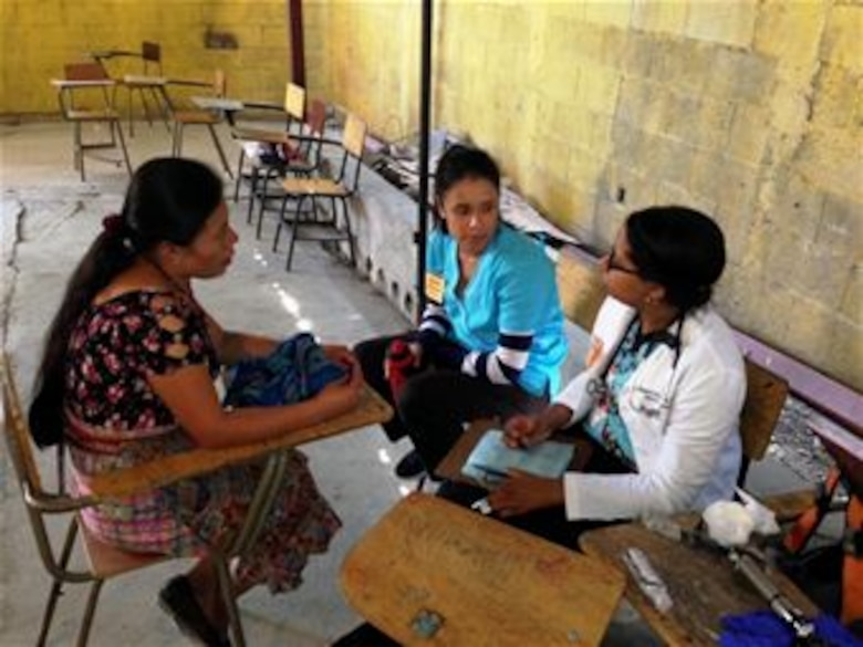 In a village near San Raimundo Guatemala, physician assistant Paree Gallo (white coat) with T.I.M.E. for Christ Medical Ministries interviews a female patient with Juany Rodriguez (right) a translator.