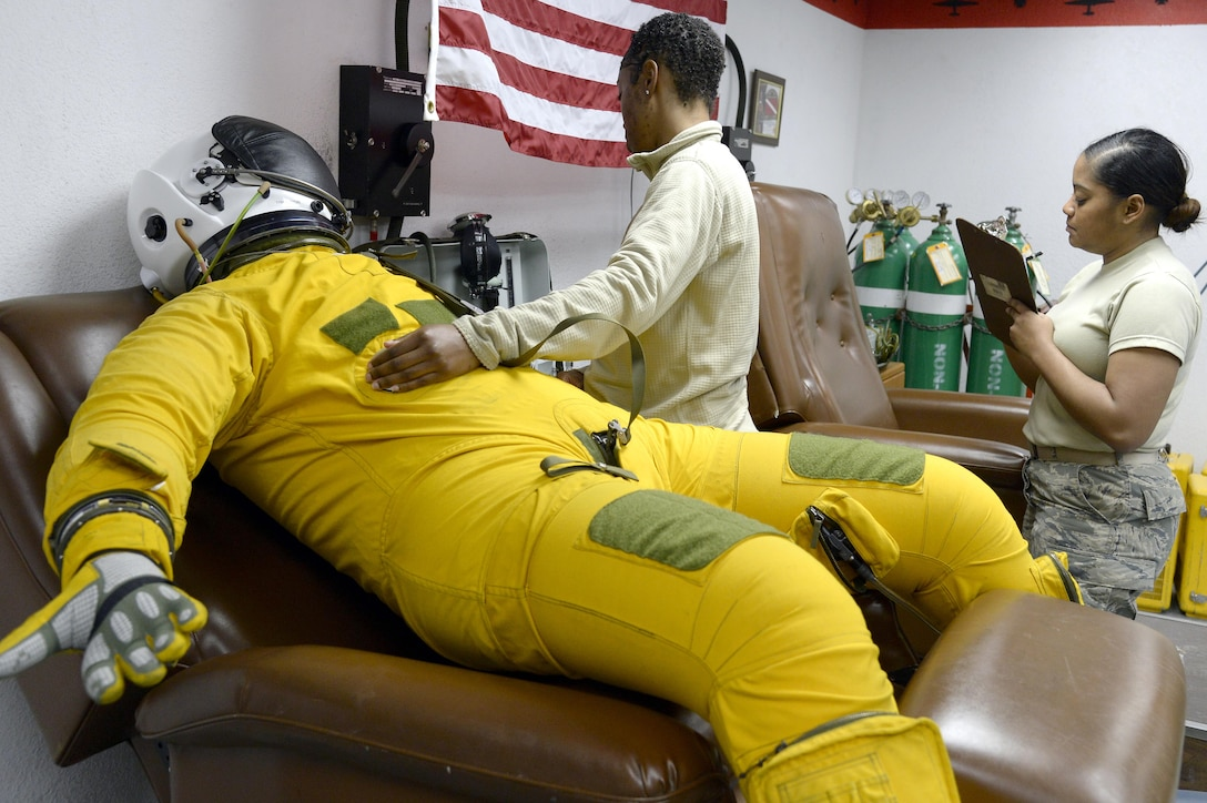 Senior Airmen Andrea, left, and Tamika, launch and recovery technicians, perform a post-flight inspection on a full pressure suit at an undisclosed location in Southwest Asia Jan. 20, 2015. Whether it is at 65,000 feet in the air or on the ground, the equipment the Airmen in the physiological support detachment maintain and inspect will aid the pilots in surviving and evading. Andrea is currently deployed from Beale Air Force Base, Calif., and is a native of Centerville, Ga. Tamika is currently deployed from Beale Air Force Base, Calif. (U.S. Air Force photo/Tech. Sgt. Marie Brown)
