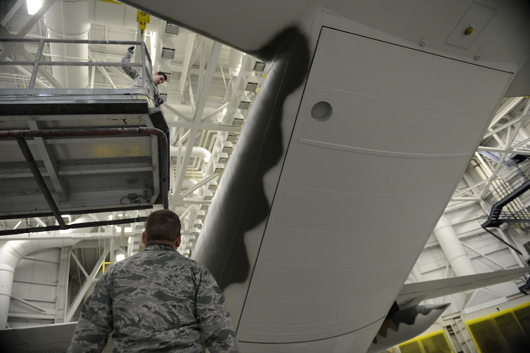 Senior Airman Justin Lounder and Senior Airman Matthew Beehler, 62nd Maintenance Squadron aircraft structural maintenance technicians repaint a C-130 Hercules Jan. 13, 2015, at Joint Base Lewis-McChord, Wash. Airmen from the 62nd MXS spent more than two months repainting a C-130 Hercules in Vietnam era camouflage scheme.  The aircraft was painted for the McChord Air Museum. (U.S. Air Force photo/Airman 1st Class Keoni Chavarria)