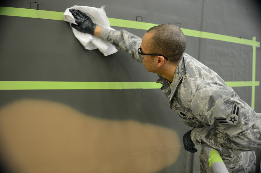 Airman 1st Class Julian Engelhardt, 62nd Maintenance Squadron structural maintenance technician, wipes dust off of a C-130 Hercules Jan. 13, 2015, during the repainting of the aircraft at Joint Base Lewis-McChord, Wash. Airmen from the 62nd MXS spent more than two months repainting the C-130 in Vietnam era camouflage scheme.  The aircraft was painted for the McChord Air Museum. (U.S. Air Force photo/Airman 1st Class Keoni Chavarria)
