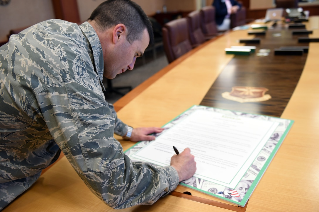 Col. John Wagner, 460th Space Wing commander, signs the pledge declaring the week of February 23-27 be Military Saves Week Jan. 22, 2015, in the SW conference room on Buckley Air Force Base, Colo. Military Saves Week is an annual opportunity for service members and their families to learn about smart financing. (U.S. Air Force photo by Airman 1st Class Emily E. Amyotte/Released)