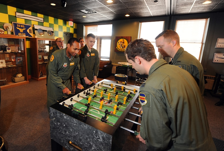 Airmen assigned to the 45th Reconnaissance Squadron play a couple of games of foosball inside their heritage room on Jan. 14, Offutt Air Force Base, Neb.  The walls geometric paint scheme is based on their unit's scarves from both the past and present.   (U.S. Air Force photo by Josh Plueger/Released)