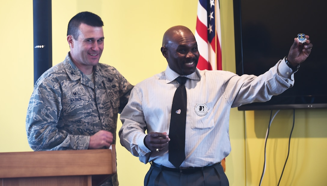 Vern L. Howard, Martin Luther King Colorado Holiday Commission chairman, spoke Jan. 22, 2015c at the Panther Den on Buckley AFB, Colo., to commemorate Dr. Martin Luther King Jr. Howard was given a 460th Space Wing coin by Col. John W. Wagner, 460th SW commander, to show appreciation for Howard's lecture on Dr. Martin Luther King Jr. (U.S. Air Force photo by Airman 1st Class Luke Nowakowski/Released)