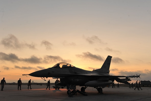 U.S. Air Force Airmen from the 180th Fighter Wing conduct a foreign object debris search, commonly referred to a FOD walk, during sunrise on the flight line of Naval Station Key West, Boca Chica Island, Florida.  FOD consists of loose objects like rocks and sticks and FOD walks helps to minimize unnecessary damage to the engine of a fighter aircraft. (Air National Guard photo by Staff Sgt. Amber Williams/Released)