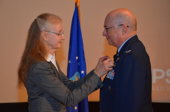 Col. (Dr.) Lewis Neace receives his official retirement pin from his wife at his retirement ceremony at Patrick Air Force Base Jan. 11, 2015. Neace completed more than 31 years of service as an Air Force Reserve physician and was most recently the commander of the 920th Aeromedical Staging Squadron at Patrick. (U.S. Air Force photo/2nd Lt. Anna-Marie Wyant)