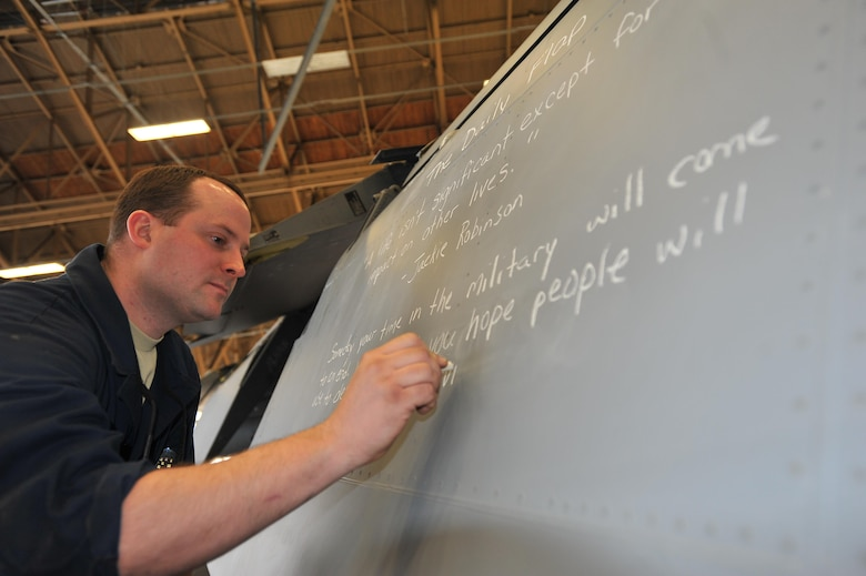 "Tech. Sgt. Eric Laflin writes an inspirational quote, referred to as the ""daily flap,"" on an aircraft's wing inboard flap Jan. 10, 2015, at Fairchild Air Force Base, Wash. Laflin began the daily flap roughly six months ago after completing the NCO professional enhancement course here to motivate and inspire Airmen in his shop. Laflin is a 141st Maintenance Squadron aircraft inspector. (U.S. Air Force photo/Staff Sgt. Veronica Montes)"