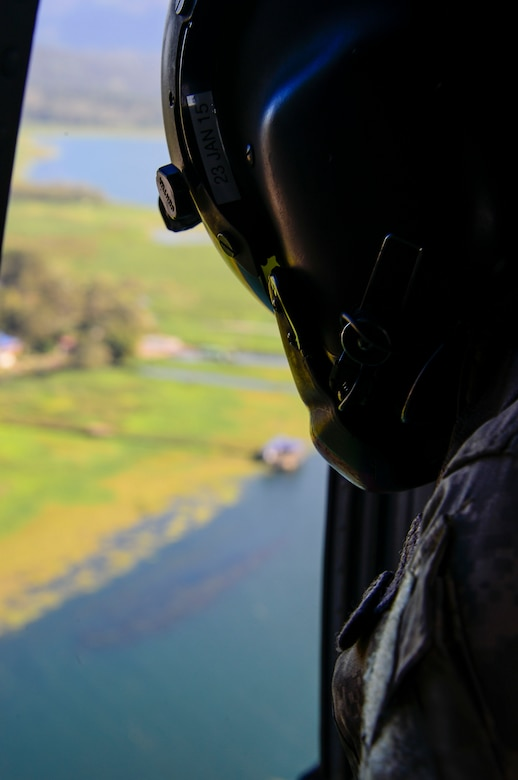 A crew chief assigned to the 1-228th Aviation Regiment looks for the U.S. Army Special Operations members in Lake Yojoa, Honduras, Jan. 22, 2015.   The 1-228th Aviation Regiment partnered with U.S. Army Special Operations personnel to practice recovering live personnel. The over-water hoist training was held to ensure members of Joint Task Force-Bravo are planning and preparing for crisis and contingency response, as well as countering transnational organized crime, and counterterrorism operations as part of U.S. Southern Command's mission. Contingency planning prepares the command for various scenarios that pose the greatest probability of challenging our regional partners or threatening our national interests. (U.S. Air Force photo/Tech. Sgt. Heather Redman)