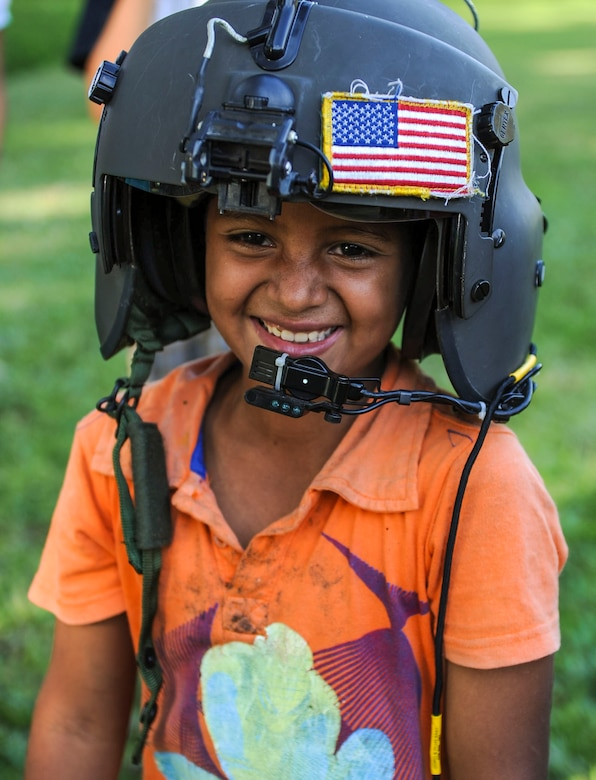 A young boy tries on an aviator helmet at Lake Yojoa, Honduras, Jan. 22, 2015.   The 1-228th Aviation Regiment partnered with U.S. Army Special Operations personnel to practice recovering live personnel. The over-water hoist training was held to ensure members of Joint Task Force-Bravo are planning and preparing for crisis and contingency response, as well as countering transnational organized crime, and counterterrorism operations as part of U.S. Southern Command's mission. Contingency planning prepares the command for various scenarios that pose the greatest probability of challenging our regional partners or threatening our national interests. (U.S. Air Force photo/Tech. Sgt. Keola Soon)