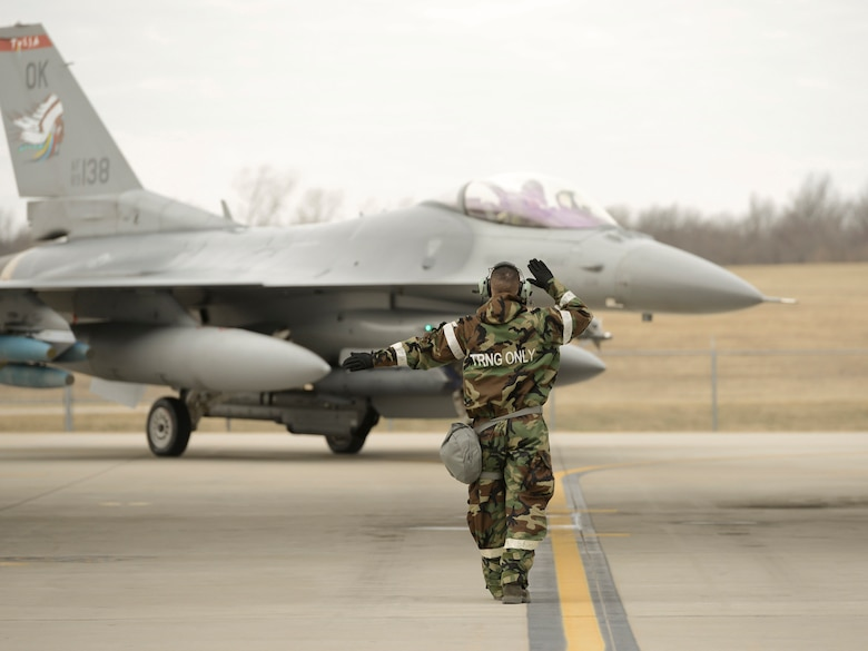 A crew chief, assigned to the 138th Maintenance Group, marshals an F-16 into its parking position during an operational readiness exercise (ORE) held, Jan. 10, 2015, at the Tulsa Air National Guard Base, Okla. The 138th Fighter Wing conducted the ORE to assess the 138th Fighter Wing's ability to accomplish design operational capability tasking in a contested, degraded operational environment utilizing ability to survive and operate principles.  (U.S. National Guard photo by Master Sgt.  Mark A. Moore/Released)