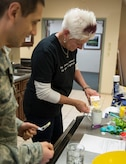 Dawn Nickerson-Banez, local bakery owner and honorary commander, measures egg mixture for quiche in a mug Jan. 21, 2015, during a microwave cooking class for service members assigned to Air Force Mortuary Affairs Operations, Dover Air Force Base, Del. The class demonstrated the healthy cooking options while living in a dorm or lodging environment. (U.S. Air Force photo by Staff Sgt. John E. Ayre)