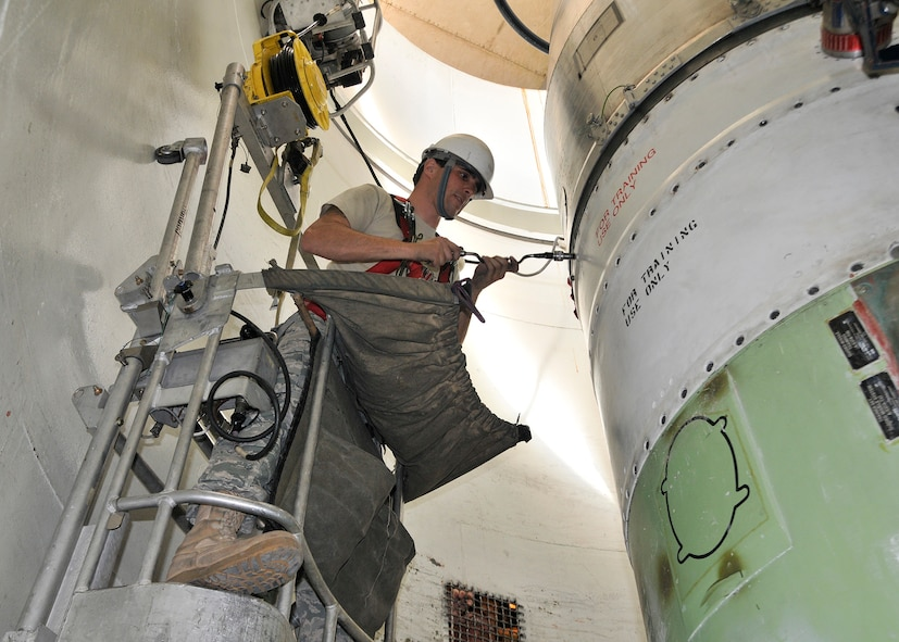 Staff Sgt. Isaiah Miller, 341st Missile Maintenance Squadron, uses a guided missile maintenance platform May 7, 2010, to remove bolts securing the reentry system on a mock-up of a Minuteman III missile during a maintenance training exercise at Malmstrom Air Force Base's T-9 launch facility maintenance trainer. (U.S. Air Force photo/John Turner)
