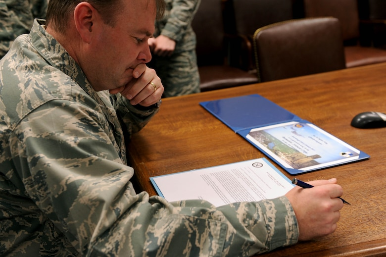 U.S. Air Force Col. Lars Hubert, 52nd Fighter Wing acting commander, reads a declaration of Biomedical Science Corps Week during a signing ceremony in the wing conference room at Spangdahlem Air Base, Germany, Jan. 21, 2015. The BSC, composed of 15 medical career fields, marks its 50th anniversary this year. (U.S. Air Force photo by Airman 1st Class Timothy Kim/Released)