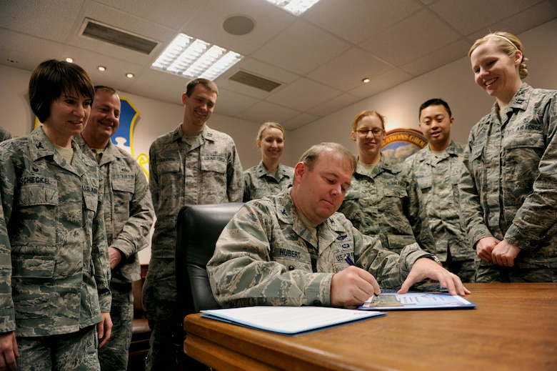 U.S. Air Force Col. Lars Hubert, 52nd Fighter Wing acting commander, signs a certificate and declaration surrounded by 52nd Medical Group Airmen in the wing conference room at Spangdahlem Air Base, Germany, Jan. 21, 2015. The proclamation designated Jan. 26-30, 2015 as Biomedical Science Corps Appreciation Week. (U.S. Air Force photo by Airman 1st Class Timothy Kim/Released)