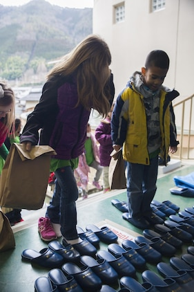 Children from the School Age Care center aboard Marine Corps Air Station Iwakuni, Japan, put on slippers provided by the Nishiki Seiryu Elementary School in Iwakuni City before entering the building, Jan. 23, 2015. SAC visited the school to compare Japanese and American schooling.