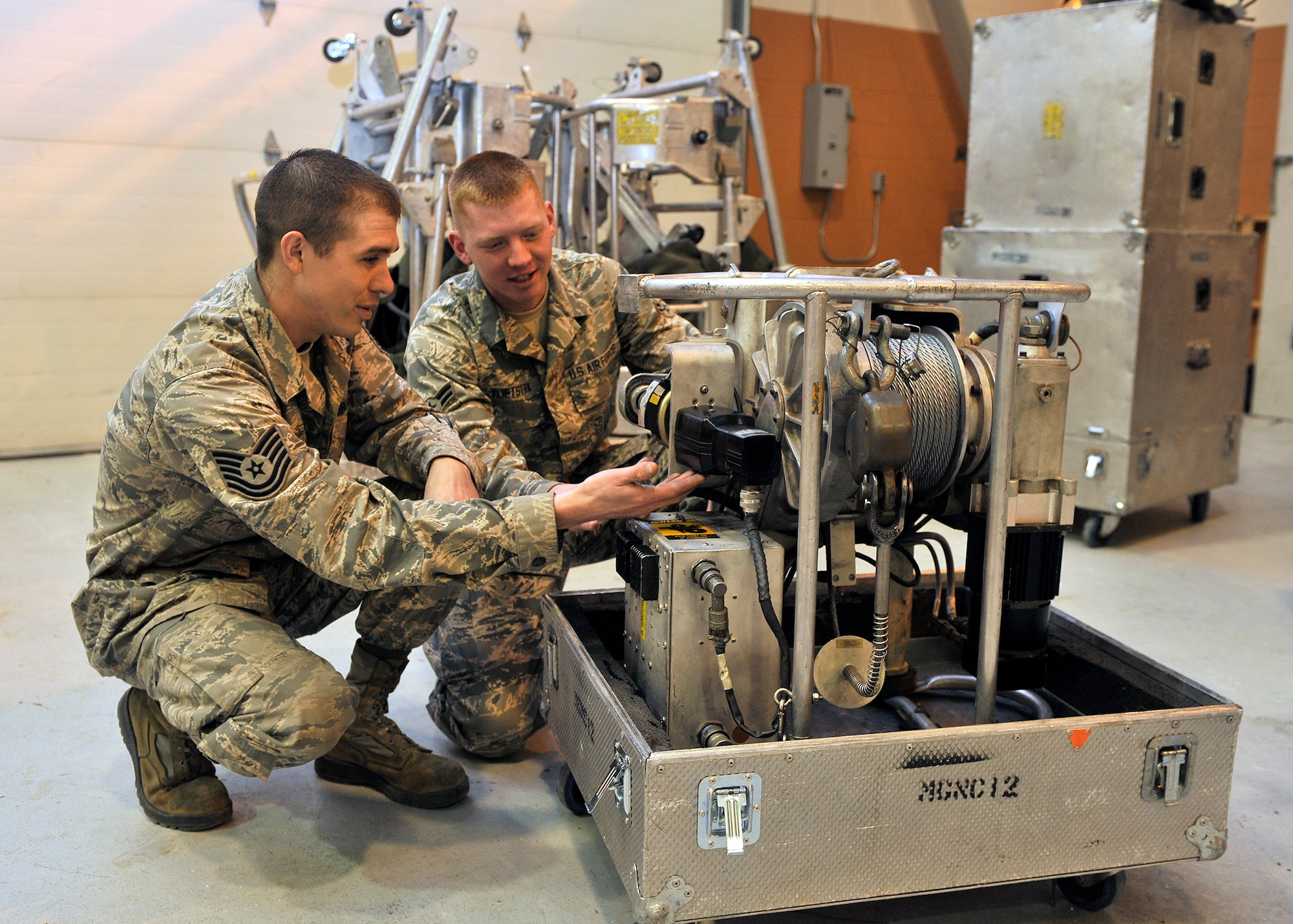 Tech. Sgt. Robert Richards and Airman 1st Class Benjamin Vlietstra  look over a guided missile maintenance platform motor Jan. 21, 2015, at Malmstrom Air Force Base, Mont. All 17 of the 341st Missile Wing's GMMPs -- also known as work cages -- were available for service Jan. 14, ensuring that missile maintenance in Minuteman III launch facilities stays on schedule. Richards is a mechanical and pneudraulics section team chief and team trainer, and Vlietstra is a power, refrigeration and electrical laboratory technician with the 341st Maintenance Operations Squadron. (U.S. Air Force photo/John Turner)