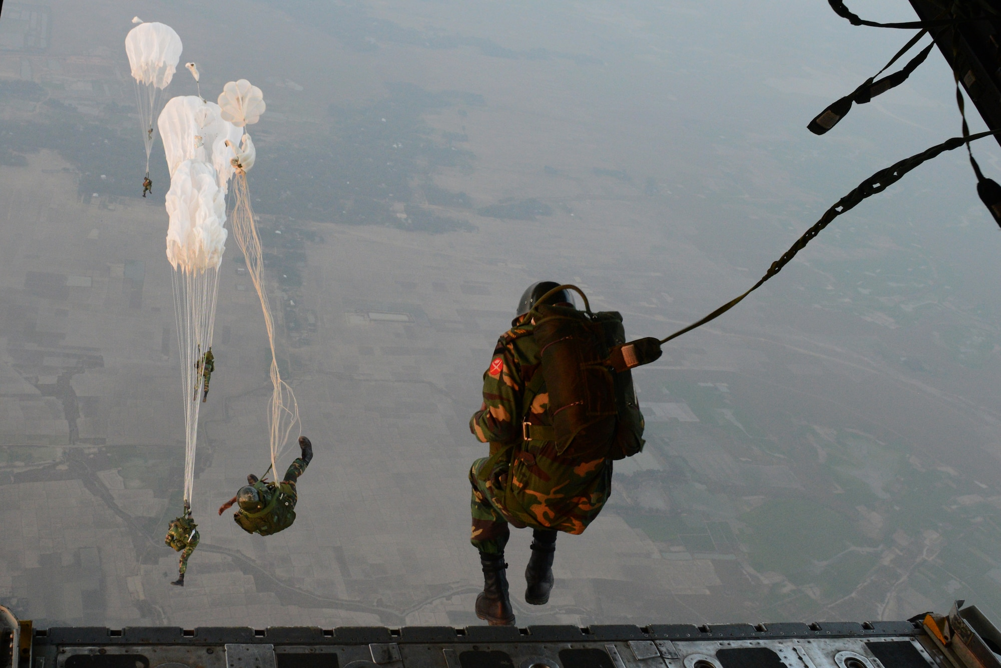 Bangladeshi commandos jump from a U.S. Air Force C-130H aircraft over a drop zone Jan. 24, 2015 during exercise Cope South near Sylhet, Bangladesh. Cope South helps cultivate common bonds, foster goodwill, and improve readiness and compatibility between members of the Bangladesh and U.S. Air Forces. (U.S. Air Force photo/1st Lt. Jake Bailey)