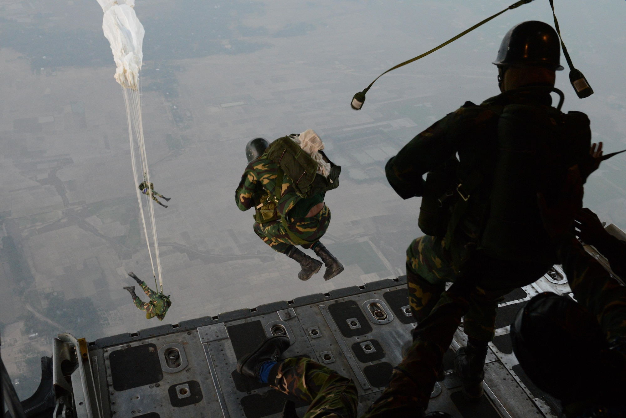 Bangladeshi commandos jump from a U.S. Air Force C-130H aircraft over a drop zone Jan. 24, 2015 during exercise Cope South near Sylhet, Bangladesh. The exercise is a Pacific Air Forces-sponsored, bilateral tactical airlift exercise conducted in Bangladesh, with a focus on cooperative flight operations, day and night low-level navigation, tactical airdrop, and air-land missions as well as subject-matter expert exchanges in the fields of operations, maintenance and rigging disciplines. (U.S. Air Force photo/1st Lt. Jake Bailey)