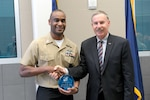 Representatives from the Colorado Springs Council of the Navy League recognized North American Aerospace Defense Command and U.S. Northern Command's Sailor of the Year during a ceremony here Jan. 27. Council President Capt. (U.S. Navy ret.) Roy Rodgers presents Petty Officer First Class Charles Harvin with a plaque in honor of his award. Harvin now competes with other combatant command nominees.