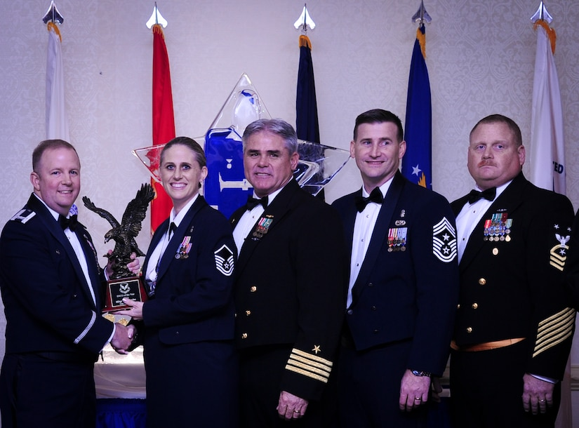 Col. Jeffrey DeVore, Joint Base Charleston commander, Capt. Timothy Sparks, JB Charleston deputy commander, Master Chief Petty Officer Joseph Gardner, Naval Support Activity command master chief and Chief Master Sgt. Mark Bronson, 628th Air Base Wing command chief present Master Sgt. Kari Boyles, 628th Aerospace Medicine Squadron, with the SNCO of the Year award Jan. 23, 2015, at the 2015 628th ABW Annual Awards Banquet at the Charleston Club on Joint Base Charleston, S.C. (U.S. Air Force photo/Airman 1st Class Clayton Cupit)