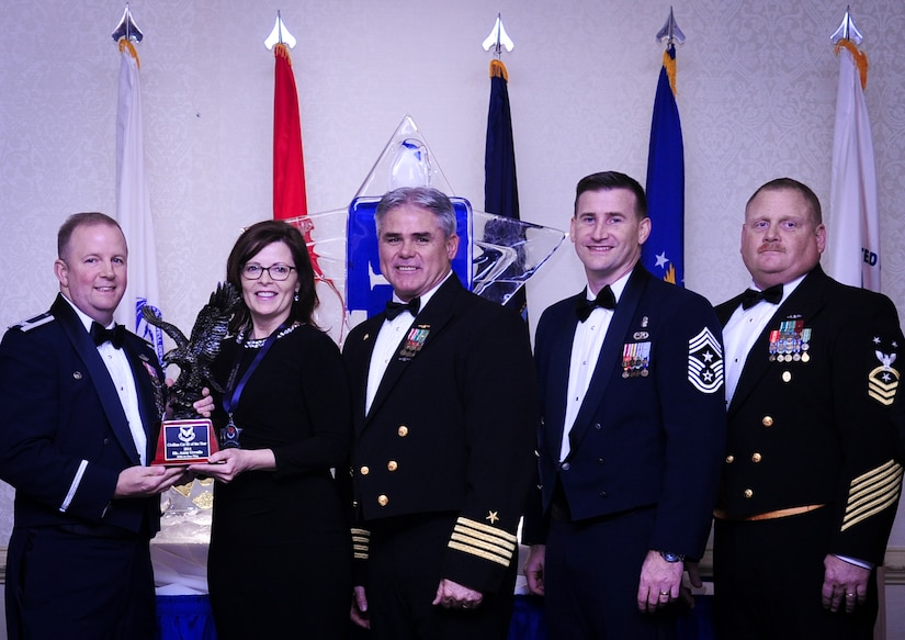 Col. Jeffrey DeVore, Joint Base Charleston commander, Capt. Timothy Sparks, JB Charleston deputy commander, Master Chief Petty Officer Joseph Gardner, Naval Support Activity command master chief and Chief Master Sgt. Mark Bronson, 628th Air Base Wing command chief present Ms. Anna Urrutia, 628th Contracting Squadron, with the Civilian Category III of the Year award Jan. 23, 2015, at the 2015 628th ABW Annual Awards Banquet at the Charleston Club on Joint Base Charleston, S.C. (U.S. Air Force photo/Airman 1st Class Clayton Cupit)