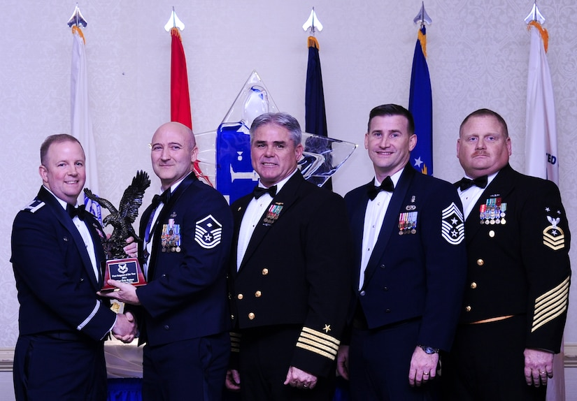Col. Jeffrey DeVore, Joint Base Charleston commander, Capt. Timothy Sparks, JB Charleston deputy commander, Master Chief Petty Officer Joseph Gardner, Naval Support Activity command master chief and Chief Master Sgt. Mark Bronson, 628th Air Base Wing command chief present Master Sgt. Eric Rainer, 628th Medical Group, with the First Sergeant of the Year award Jan. 23, 2015, at the 2015 628th ABW Annual Awards Banquet at the Charleston Club on Joint Base Charleston, S.C. (U.S. Air Force photo/Airman 1st Class Clayton Cupit)
