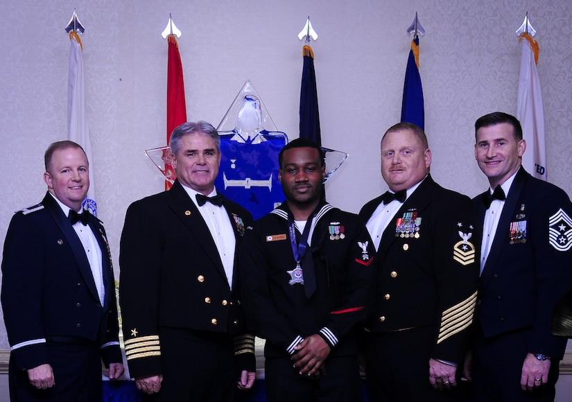 Col. Jeffrey DeVore, Joint Base Charleston commander, Capt. Timothy Sparks, JB Charleston deputy commander, Master Chief Petty Officer Joseph Gardner, Naval Support Activity command master chief and Chief Master Sgt. Mark Bronson, 628th Air Base Wing command chief stand with Logistics Specialist 3rd Class Delmetrius Blanding, NSA, Blue Jacket of the Year, Jan. 23, 2015, at the 2015 628th ABW Annual Awards Banquet at the Charleston Club on Joint Base Charleston, S.C. (U.S. Air Force photo/Airman 1st Class Clayton Cupit)