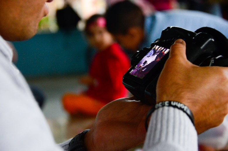 U.S. Air Force Tech. Sgt. Keola Soon, assigned to the 612th Air Base Squadron, looks at a photo he took during Joint Task Force-Bravo's visit to at the Sisters of Charity Orphanage in Comayagua, Honduras, Jan. 25, 2015. The Sisters of Charity Orphanage is one of seven different orphanages from around the Comayagua Valley that the U.S. military personnel assigned to JTF-Bravo have supported over the past 17 years. In addition to spending time with interacting with children, members have also collected and donated much-needed supplies and food, as well as helped in minor construction work on the buildings in which the children live. (U.S. Air Force photo/Tech. Sgt. Heather Redman)