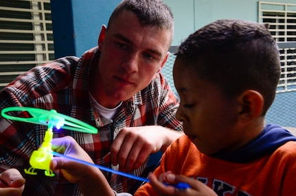 U.S. Marine Corps 1st Lt. Ryan Lee, assigned to Marine Corps Forces Southern, helps a young boy with a toy during Joint Task Force-Bravo's visit to at the Sisters of Charity Orphanage in Comayagua, Honduras, Jan. 25, 2015. The Sisters of Charity Orphanage is one of seven different orphanages from around the Comayagua Valley that the U.S. military personnel assigned to JTF-Bravo have supported over the past 17 years. In addition to spending time with interacting with children, members have also collected and donated much-needed supplies and food, as well as helped in minor construction work on the buildings in which the children live. (U.S. Air Force photo/Tech. Sgt. Heather Redman)