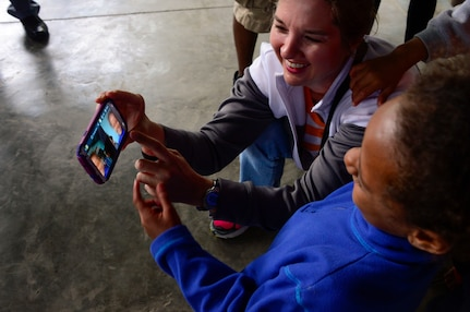 U.S. Army Maj. Rhonda Dyer, assigned to Joint Task Force-Bravo's Medical Element, shows a young girl how to take a selfie photograph during JTF-Bravo's visit to at the Sisters of Charity Orphanage in Comayagua, Honduras, Jan. 25, 2015. The Sisters of Charity Orphanage is one of seven different orphanages from around the Comayagua Valley that the U.S. military personnel assigned to JTF-Bravo have supported over the past 17 years. In addition to spending time with interacting with children, members have also collected and donated much-needed supplies and food, as well as helped in minor construction work on the buildings in which the children live. (U.S. Air Force photo/Tech. Sgt. Heather Redman)