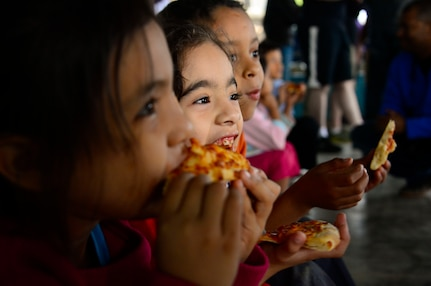 A group of children enjoy their pizza dinner during Joint Task Force-Bravo's visit to at the Sisters of Charity Orphanage in Comayagua, Honduras, Jan. 25, 2015. The Sisters of Charity Orphanage is one of seven different orphanages from around the Comayagua Valley that the U.S. military personnel assigned to JTF-Bravo have supported over the past 17 years. In addition to spending time with interacting with children, members have also collected and donated much-needed supplies and food, as well as helped in minor construction work on the buildings in which the children live. (U.S. Air Force photo/Tech. Sgt. Heather Redman)
