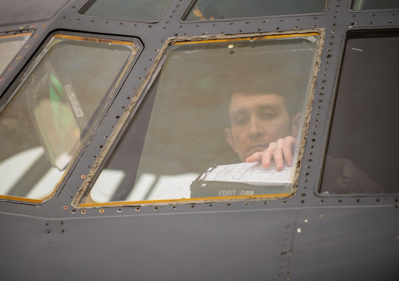 Capt. Kenneth Jubb, 37th Airlift Squadron pilot, reaches for his clipboard to review flight plans during a training mission in a C-130J Super Hercules Jan. 22, 2015, at Ramstein Air Base, Germany. The intent of the mission was to train Jubb and the co-pilot in flying at 7,000 feet as well as performing a simulated cargo drop to maintain proficiency. (U.S. Air Force photo/Senior Airman Jonathan Stefanko)