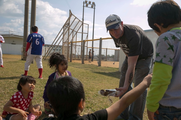 Gunnery Sgt. Jonathan K. Ivy, from Dimmitt, Texas, offers cookies to Okinawan children during a cookout following a friendly softball game between the Henoko Young Men's Association and U.S. Marines Jan. 25 on Camp Schwab. Ivy is the company gunnery sergeant for Company K, 3rd Battalion, 3rd Marine Regiment, currently assigned to 4th Marine Regiment, 3rd Marine Division, III Marine Expeditionary Force under the unit deployment program. The children are residents of Henoko, Okinawa.