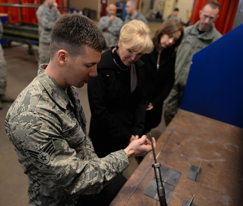 Senior Airman William Greenway demonstrates welding procedures with retired Chief Master Sgt. Athena Cody, wife of Chief Master Sgt. of the Air Force James A. Cody, Jan. 23, 2015, on Barksdale Air Force Base, La. During her two-day visit, Cody toured the base and visited several different squadrons to speak with Airmen and experience their day-to-day duties. Greenway is a 2nd Maintenance Squadron metals technician journeyman. (U.S. Air Force photo/Airman 1st Class Curt Beach)