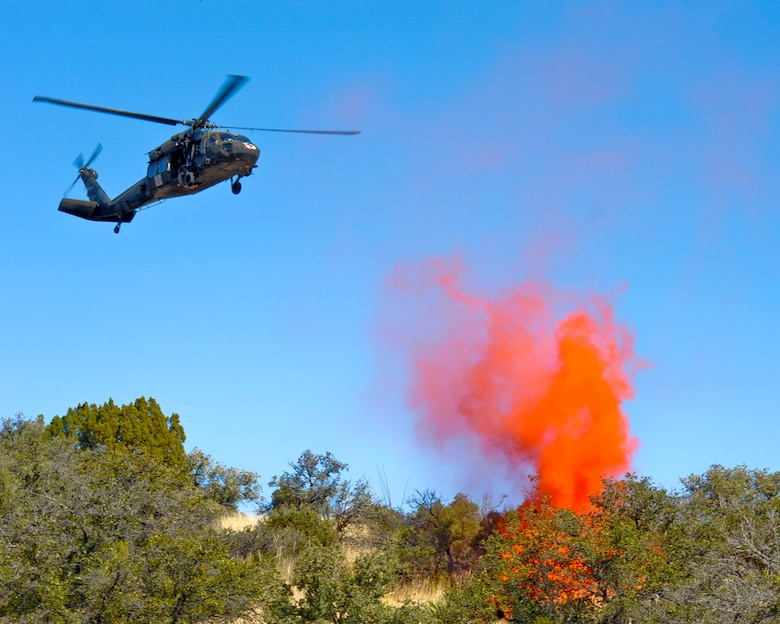 An Arizona Army National Guard UH-60A Black Hawk helicopter from Detachment 1, C Company, 5-159th Air Ambulance, based out of Phoenix, hovers over smoke from a flare at a military training range in southern Arizona, Jan. 20, 2015.  The flare signified the location of a simulated downed pilot during a joint service close air support and combat search and rescue exercise. (U.S. Air Force Photo by Airman 1st Class Chris Massey/Released)