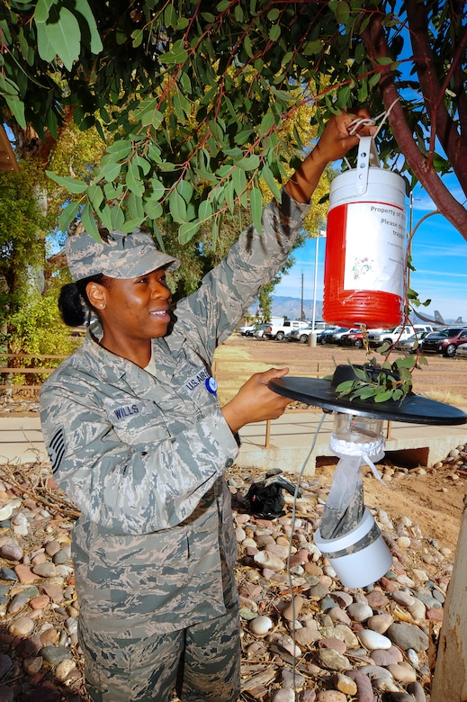 U.S. Air Force Tech. Sgt. Patrice Wills, 355th Aerospace Medicine Squadron community health element chief, sets up a mosquito trap for infectious disease testing at Davis-Monthan Air Force Base, Ariz., Jan. 28, 2015. The Biomedical Sciences Corps encompasses 15 Air Force Specialty Codes, with 10 of those AFSC's practiced at D-M. The 355th Medical Group is celebrating Biomedical Sciences Corps Appreciation week in conjunction with the Corps' 50th anniversary. (U.S. Air Force photo by Staff Sgt. Angela Ruiz)