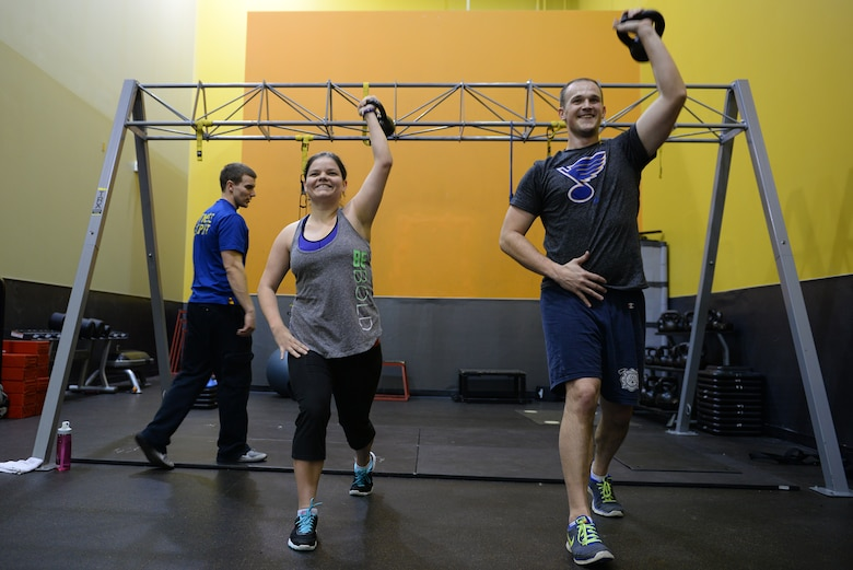 Jessi McNulty, 26, and her husband Staff Sgt. Stephen McNulty, a 375th Civil Engineering Squadron Firefighter, performs kettle bell lunges at their gym, O'Fallon, Ill., Jan. 22, 2015. Jessi has been hitting this gym for nearly two years, during which time she has lost 90 pounds despite having temporal lobe epilepsy. Generally her workouts are total-body-oriented and her and her personal trainer monitors her heart rate to mitigate her seizures, which are exercise-induced. (U.S. Air Force photo by Airman 1st Class Erica Crossen)