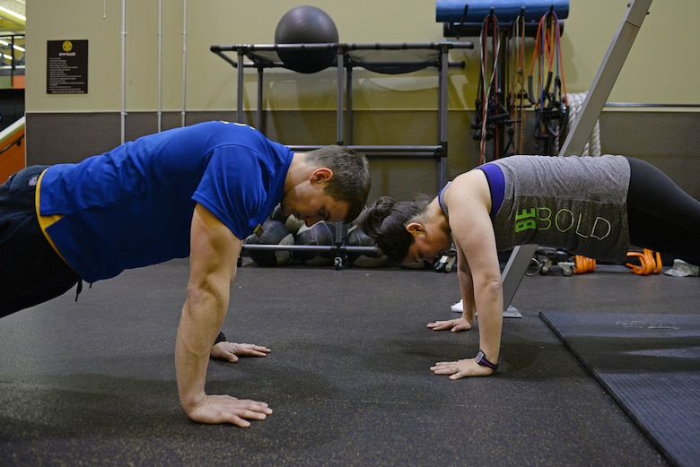 Jessi McNulty, 26, uses TRX straps at her gym in a plank position with her personal trainer Nate Myers, O'Fallon, Ill., Jan. 22, 2015. This Air Force spouse has been hitting this gym for nearly two years, during which time she has lost 90 pounds despite having temporal lobe epilepsy. Generally her workouts are total body-oriented. She and Myers monitors her heart rate to mitigate her seizures, which are exercise-induced. (U.S. Air Force photo by Airman 1st Class Erica Crossen)