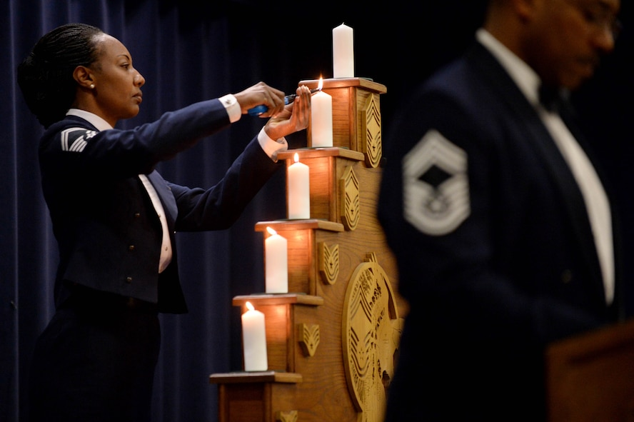 U.S. Air Force Senior Master Sgt. Dana Butler, 52nd Medical Support Squadron superintendent and native of Georgetown, S.C., lights a candle as part of the progression of ranks ceremony during the Chief Master Sergeant Recognition Ceremony in Club Eifel at Spangdahlem Air Base, Germany, Jan. 23, 2015. The candle-lighting ceremony illustrates each rank that the chief master sergeant selects went through attain the highest enlisted rank. (U.S. Air Force photo by Airman 1st Class Timothy Kim/Released)