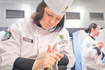 Pfc. Amber Tomlin, 97th MP Bn., slices garlic Jan. 15 at Fort Riley's Food Service lab as part of the Student Chef Cookoff.